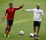 Bayern Munich new head coach Guardiola  points to player Mueller during his first team training session in Munich