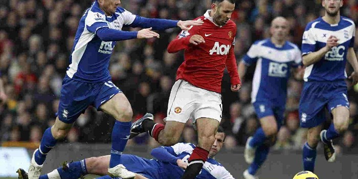 Manchester United's Giggs challenges Birmingham City's Ferguson and Fahey during their English Premier League soccer match at Old Trafford in Manchester
