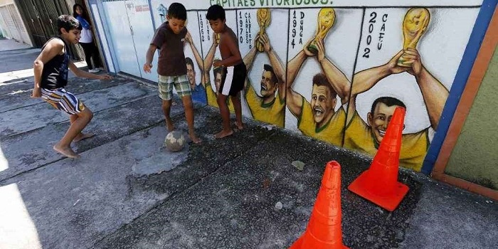 Boys play with a soccer ball next to graffiti painted in reference to Brazil's five World Cup titles in Rio de Janeiro