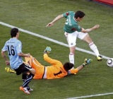 Mexico's Franco tries to score past Uruguay's goalkeeper Muslera during a 2010 World Cup Group A soccer match at Royal Bafokeng stadium in Rustenburg