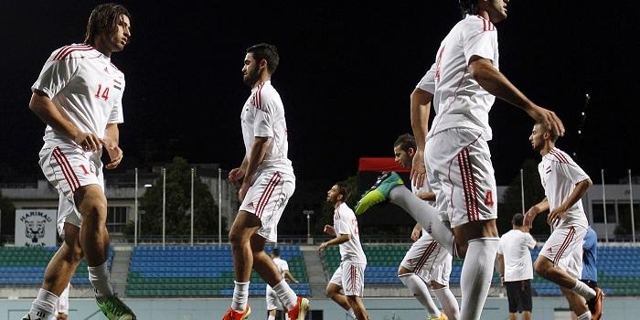 Syria's soccer squad warm up during training at Jalan Besar Stadium in Singapore